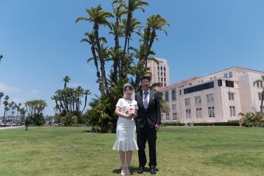 샌디에고 카운티 센터 앞에서 신랑 신부가 결혼 기념 사진을 찍는다